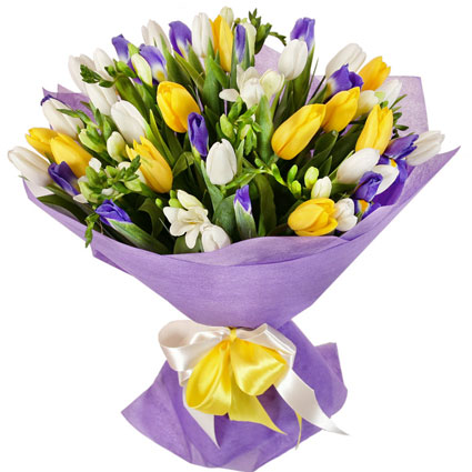 Flowers. Colorful bouquet of yellow tulips, white tulips, blue iris, white freesias in decorative packaging.