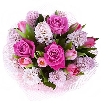 Ziedi ar kurjeru. Skaists ziedu pušķis maigi rozā toņos no rozēm, tulpēm un hiacintēm dekoratīvā saiņojumā.  Ziedu klāsts