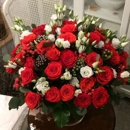 Ziedu veikals. Krāšņajā ziedu pušķī 30 sarkanas rozes, 15 baltas lizantes, dekoratīvās bouvardijas un brunijas.   Ziedu