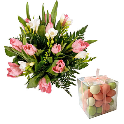 """Bouquet of pink tulips, white freesias and decorative foliage and """"AL MARI ANNI"""" chocolate dragees. Peanuts, blueberries, rhubarb in white c"""