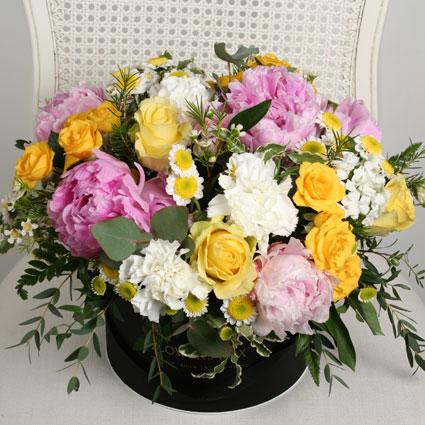 Ziedi un to piegāde. Rozā peonijas, dzeltenas rozes  un balti smalkziedi ar dekoratīviem zaļumiem ziedu kastītē.  Ziedu