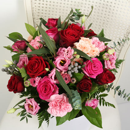 Flowers on-line. Flower bouquet of red and pink roses, pink lisianthus and pink carnations with decorative seasonal foliage.