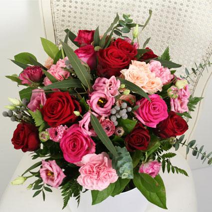 Ziedi. Ziedu pušķis no sarkanām un rozā rozēm, rozā lizantēm un neļķēm ar dekoratīviem sezonāliem zaļumiem.  Ziedu klāsts