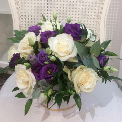 Ziedu piegāde. Ziedu kastītē baltas rozes, zilas lizantes un dekoratīvi zaļumi.  Ziedu klāsts ir ļoti plašs. Var gadīties,