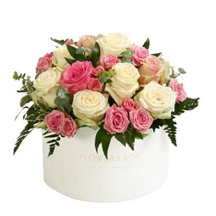 Ziedi Latvijā. Ziedu kārbā rozā un baltas  rozes, rozā krūmrozes, baltas lizantes un dekoratīvi zaļumi. ø 30 cm  Ziedu