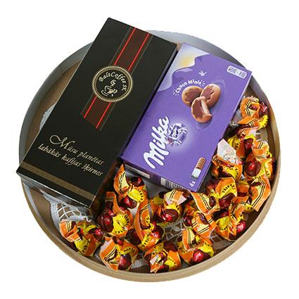 Ziedi ar kurjeru. Dāvanu komplekts: malta kafija 250 g, Laimas šokolādes konfektes Trifeles 160 g un  cepumi Milka