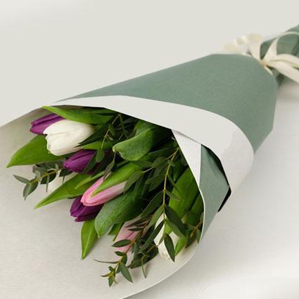 Pavasarīgs tulpju un sezonas zaļumu pušķītis dekoratīvā saiņojumā.