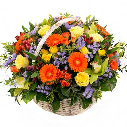 Ziedi un to piegāde. Krāšņa ziedu kompozīcija pītā grozā no dzeltenām un oranžām krūmrozēm, dzeltenām rozēm, zaļām