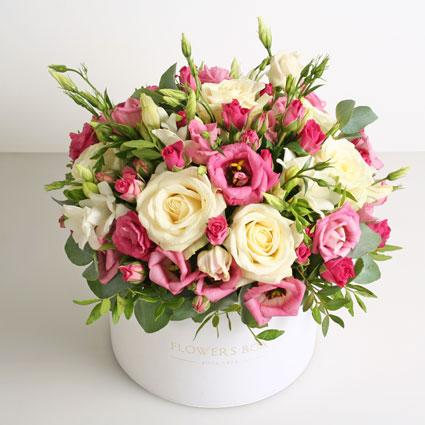 Ziedu piegāde Rīgā, ziedu kārbā baltas un rozā rozes, rozā lizantes, baltas frēzijas un dekoratīvi zaļumi 30 cm garumā