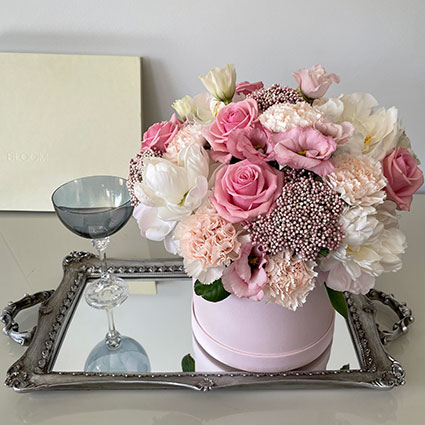 Ziedu kārbā rozā un violetas  rozes,  baltas neļķes un dekoratīvi zaļumi