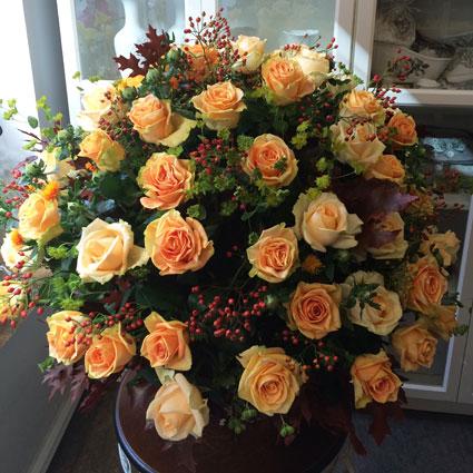 Ziedu piegāde Rīgā, apjomīgā pušķī krēmkrāsas rozes, dekoratīvas ogas un sezonas zaļumi