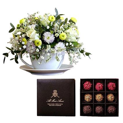 """Ziedu kompozīcija baltā porcelāna krūzītē un """"AL MARI ANNI"""" šokolādes trifeles 135 g (aveņu, karameļu, pistāciju)."""