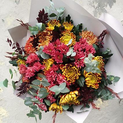 Ziedu pušķis rudenīgā krāsu gammā no lielziedu un daudzziedu krizantēmām ar dekoratīviem sezonas zaļumiem