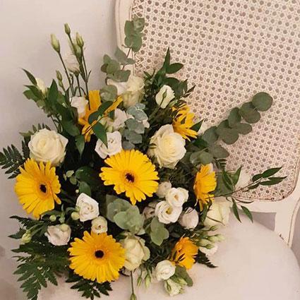 Ziedi un to piegāde. Ziedu pušķī baltas rozes, dzeltenas gerberas, baltas lizantes un dekoratīvi zaļumi.  Ziedu klāsts ir