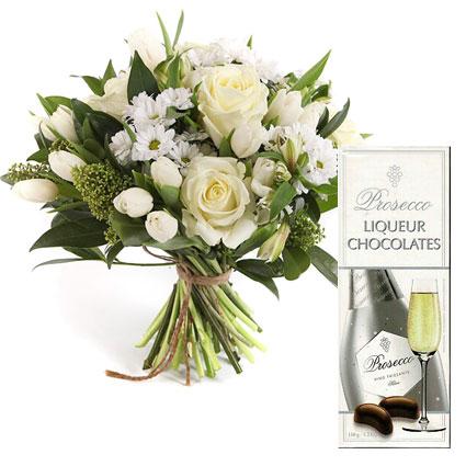 """Baltu ziedu pušķis: rozes, tulpes, alstromērijas, smalkziedu krizantēmas, kā arī Santini un """"Doulton"""" šokolādes liķiera konfektes"""