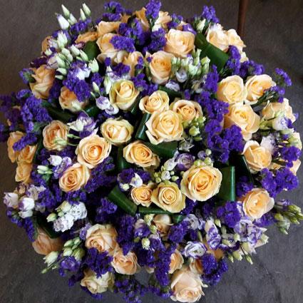 Ziedi ar kurjeru. Grezns, apjomīgs ziedu pušķis no gaišām rozēm, balti-zilām lizantēm, zilām limonijām un dekoratīvām
